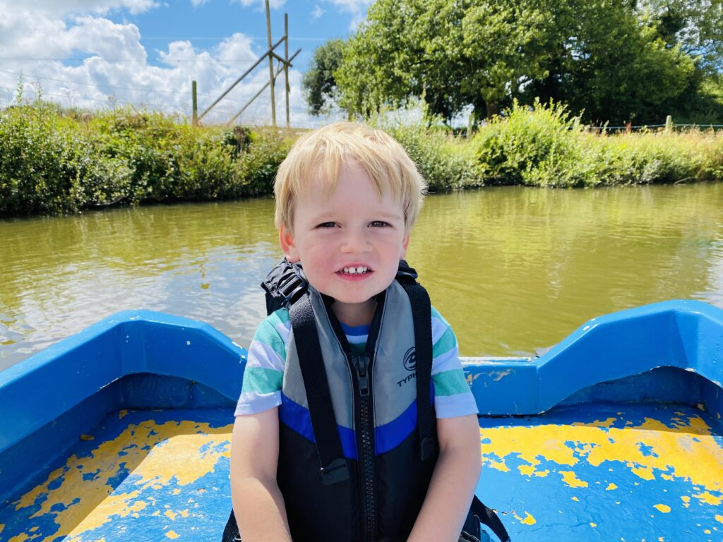 Three year old boy in a rowing boat on a boating lake at Springfields fun park