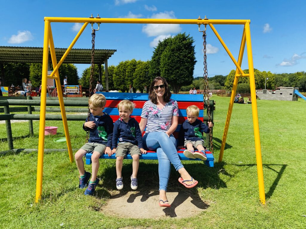Mum and three boys on a swinging seat at Springfields fun park