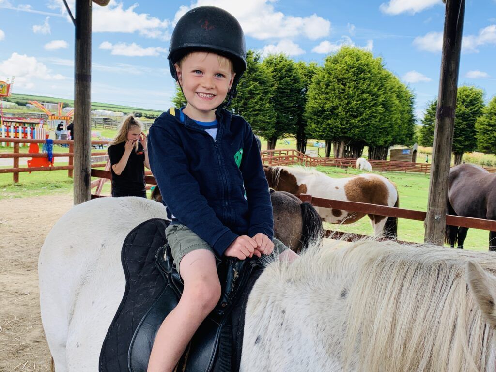 Five year old boy happy on a pony ride