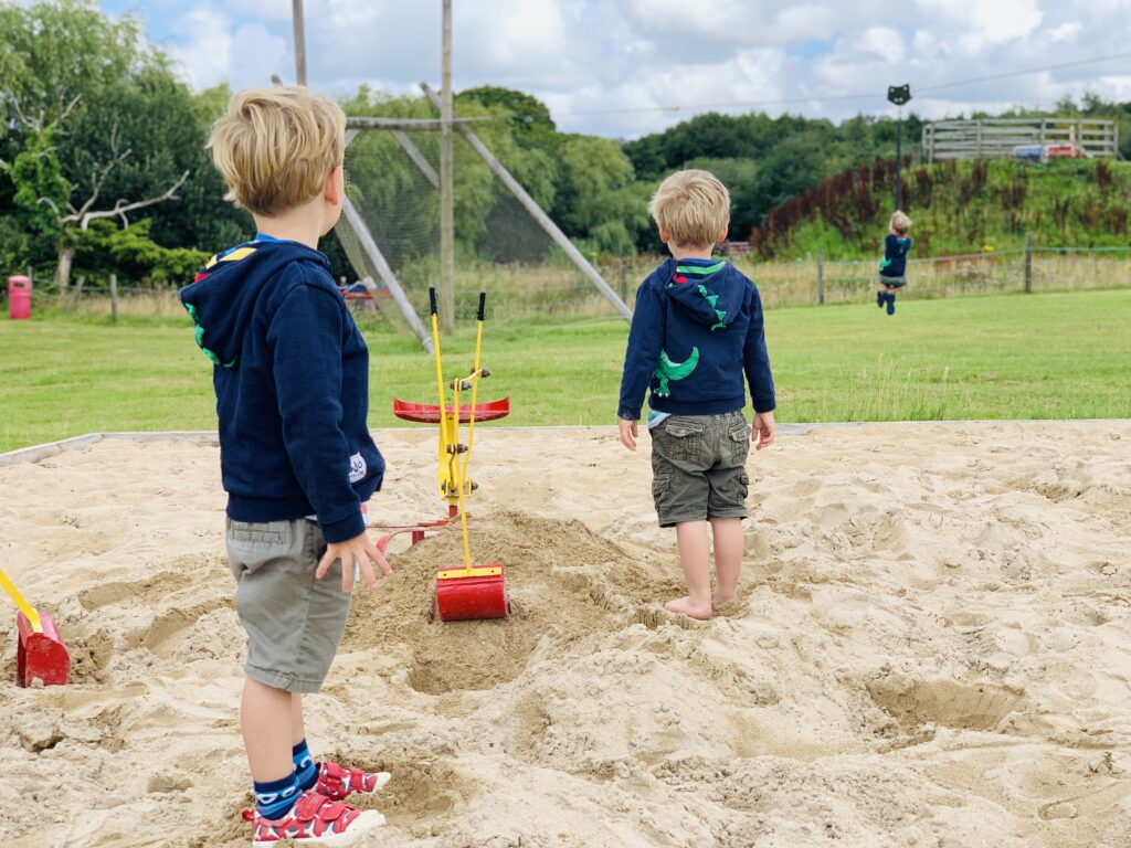Three year old twins play in a sandpit and watch their older brother on a zip wire in the background