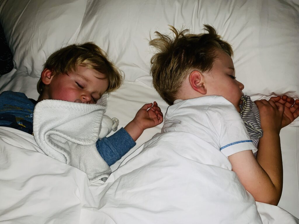 Brothers asleep in their mum and dad's bed