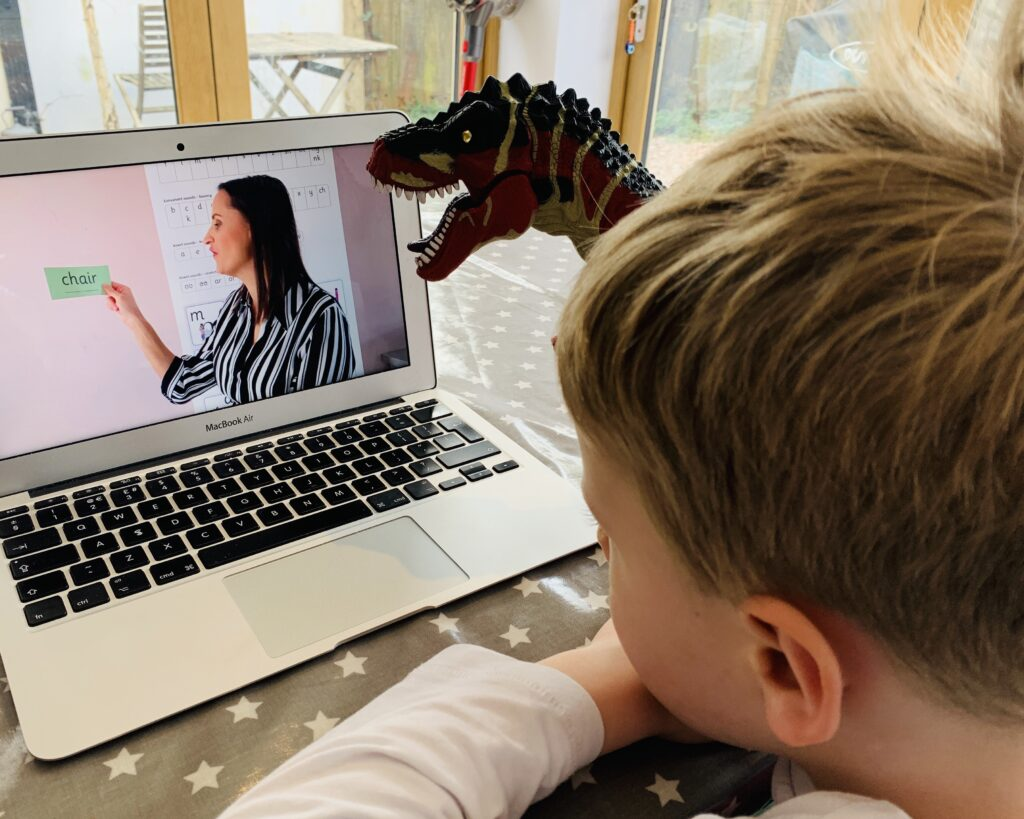 Five year old watches a phonics video before going back to school during Covid