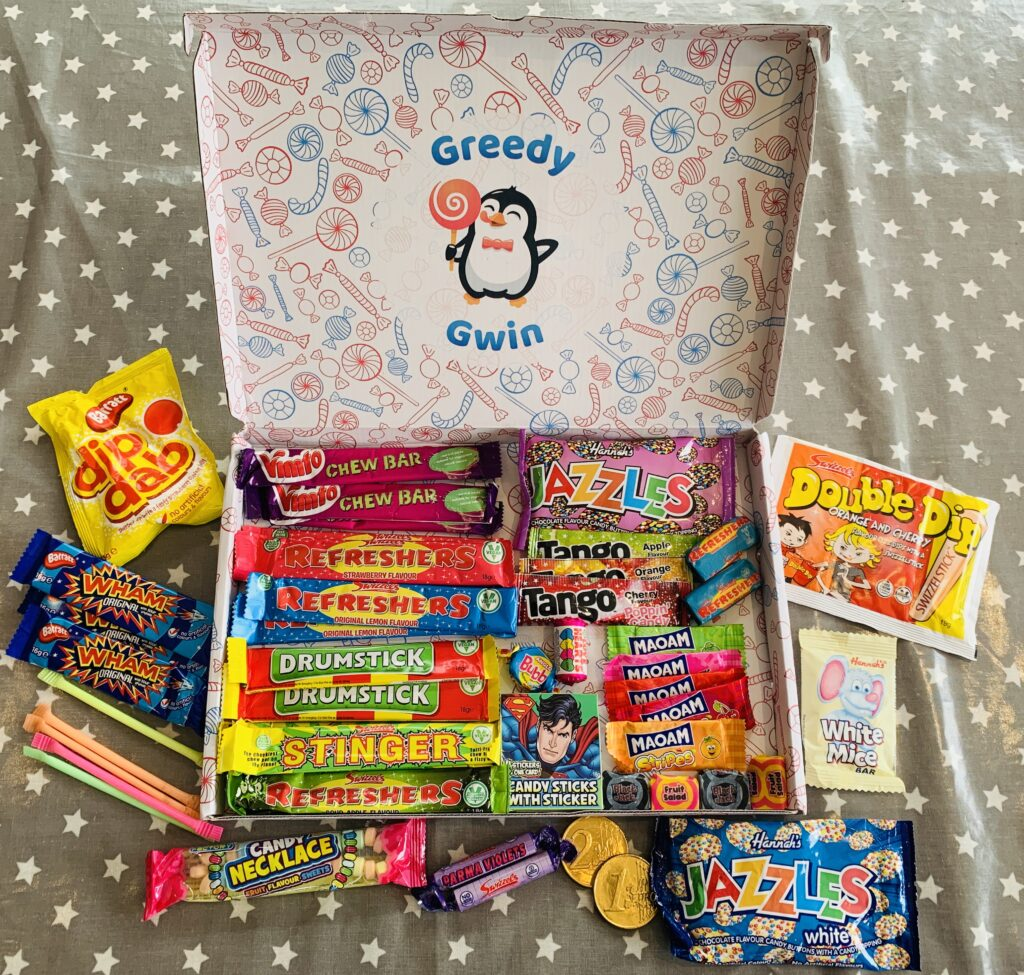 A cardboard hamper filled with lots of packets of retro sweets