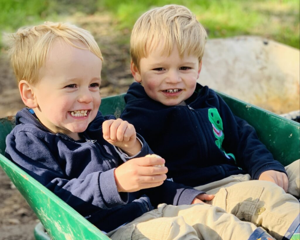 Twin boys aged 3 wearing navy blue hoodies sitting in a wheelbarrow at a halloween pumpkin patch and laughin