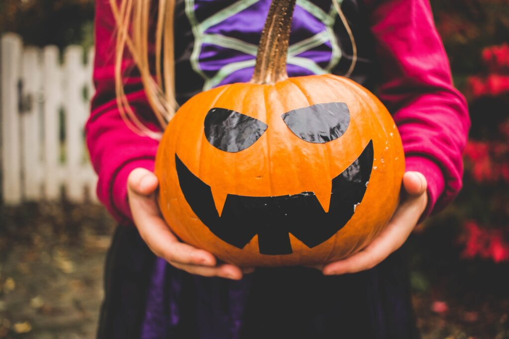 A pair of child's hands holding a pumpkin with a black face on it