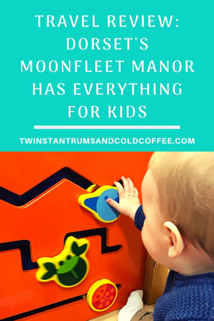 PIN image, little baby boy playing with a wooden wall toy at Dorset's Moonfleet Manor