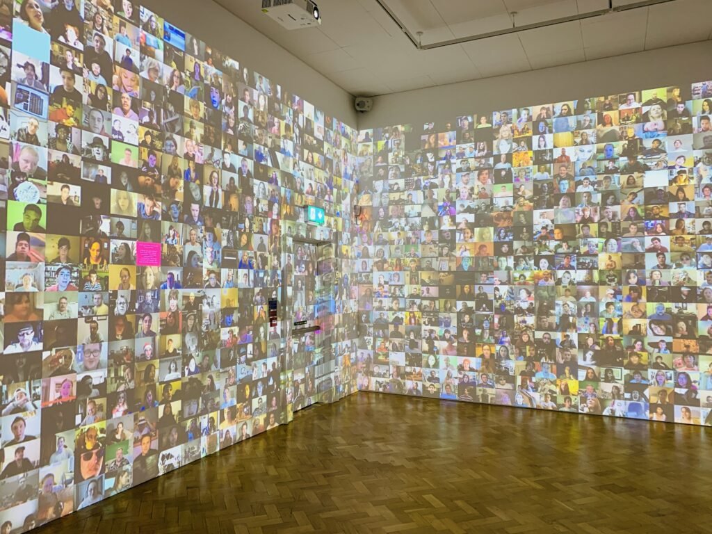A room with all walls to ceiling covered in a digital display of moving images and faces at The Box in Plymouth