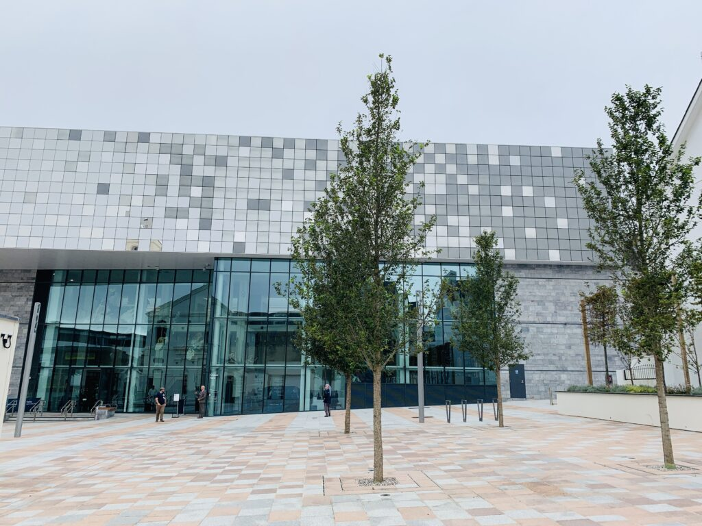 Modern building made up of tiny square pieces of glass on top of an old building to create the new museum The Box in Plymouth, with a tree and paving outside.
