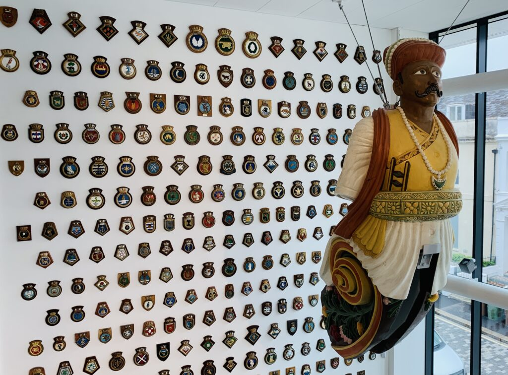 A giant wooden figureheads from naval ships preserved and restored hanging from the ceiling of The Box museum in Plymouth. The wall behind is covered with naval badges