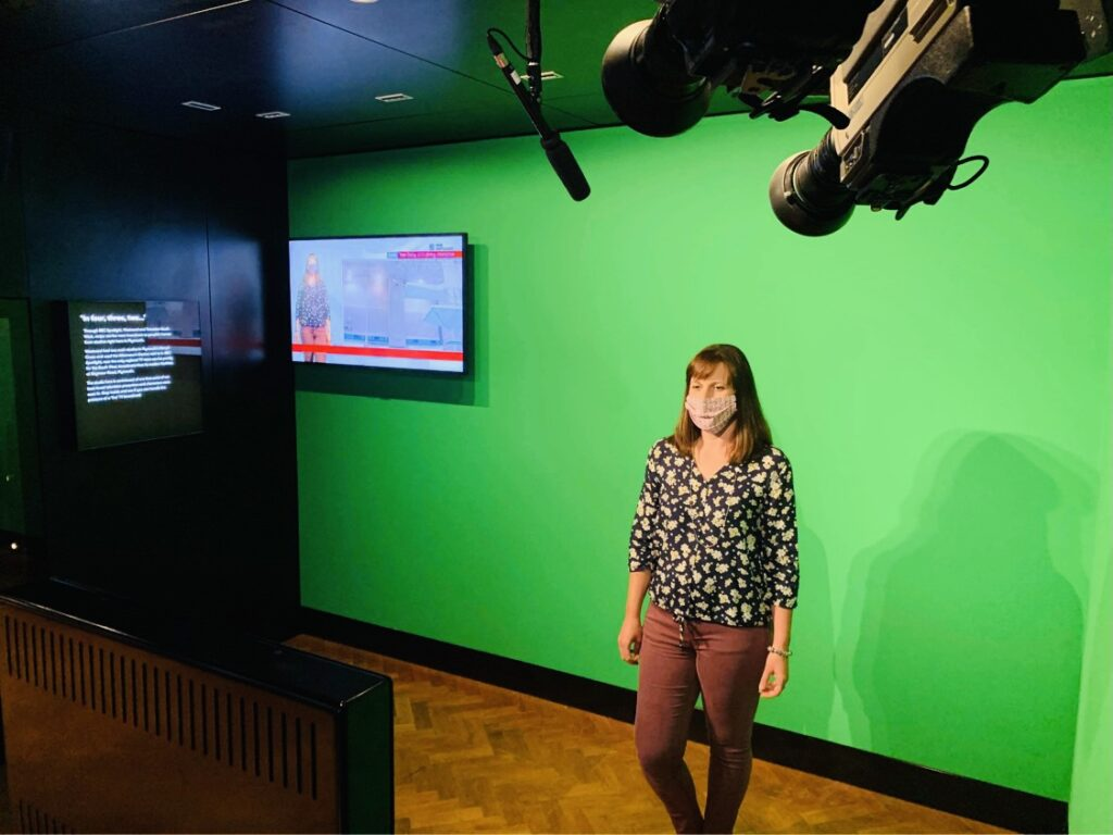 A woman wearing a face mask stands in a mock TV studio reading the news at The Box in Plymouth