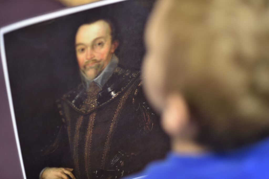 The back of a head of a child looking at an old painting of a man as a part of an educational programme at The Box in Plymouth