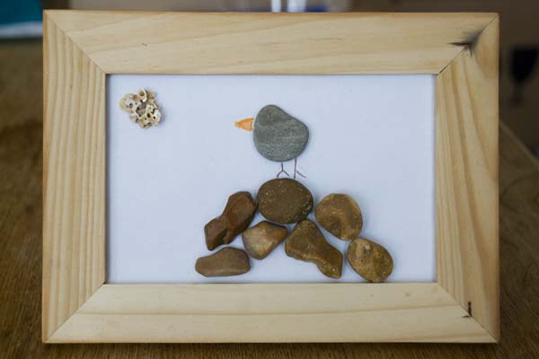 A wooden picture frame with a white sheet of paper inside with small flat pebbles stuck to it arranged in a picture to show a bird sat on a pile of rocks