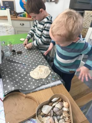 A six year old and two year old boys in stripy tops making salt dough dinosaur fossils at a table with a grey and white table cloth. One of many easy craft ideas