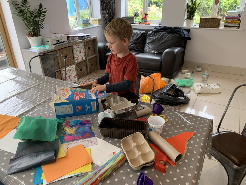 A five year old boy at a kitchen table with a settee in the background doing junk modelling. The table and floor behind him is strewn with items of recycling such as cereal boxes, plastic bottles, paper, egg boxes, yoghurt pots and kitchen roll holders.