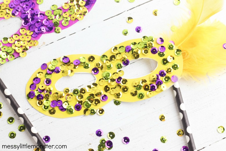 Yellow mardi gras mask decorated with sequins and glitter is a an easy craft idea for children