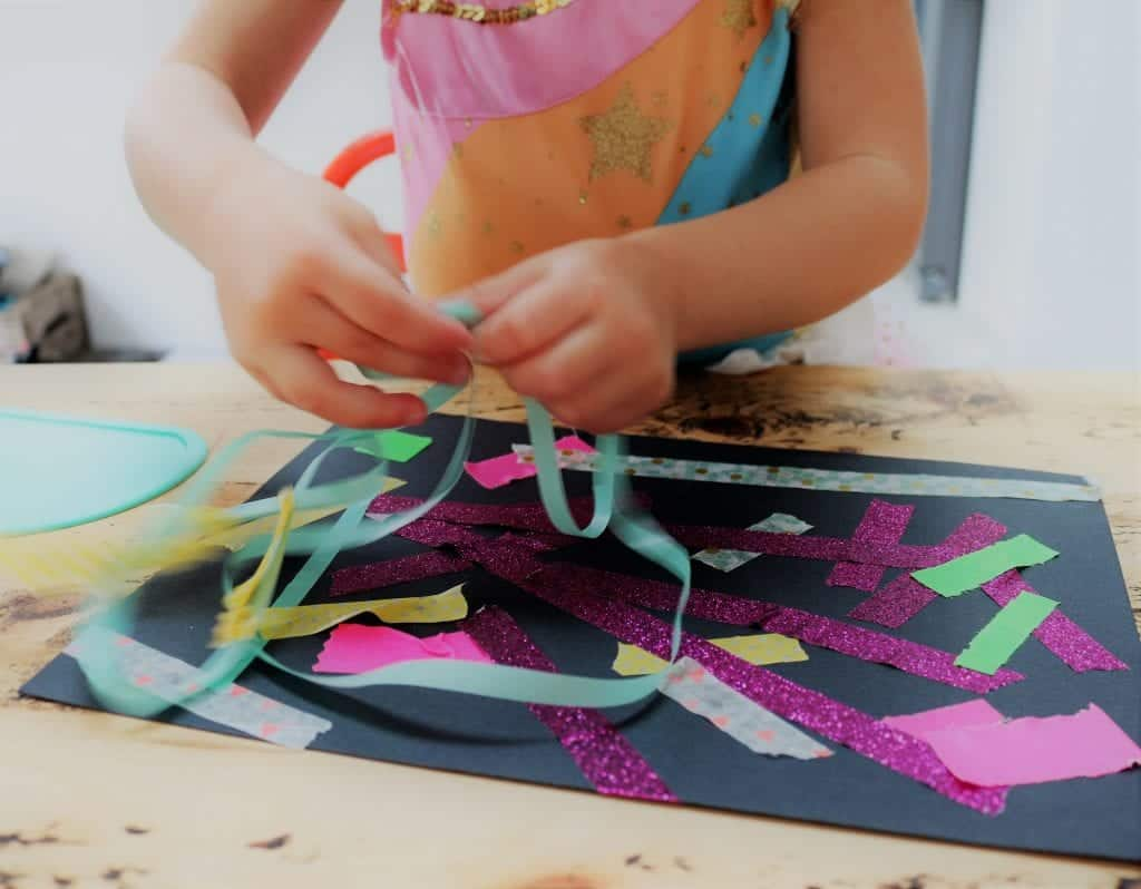 A girl's hands ripping washi tape in different colours and sticking it to a black sheet of paper to make mess free firework pictures