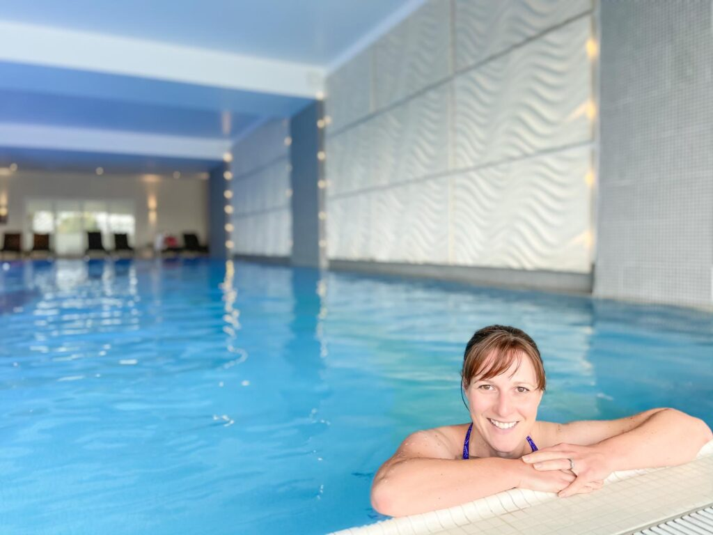 Woman with dark hair leaning on the side of a Holiday Inn hotel swimming pool on a spa break with friends