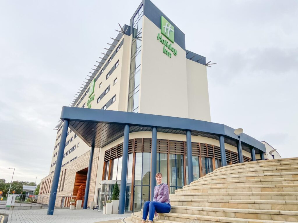 A woman in jeans and stripy jumper sat on some steps outside a tall Holiday Inn building