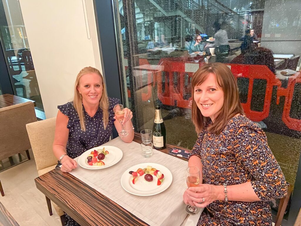 Two women sat at a table in the window of a restaurant with a plate of food and glass of champagne