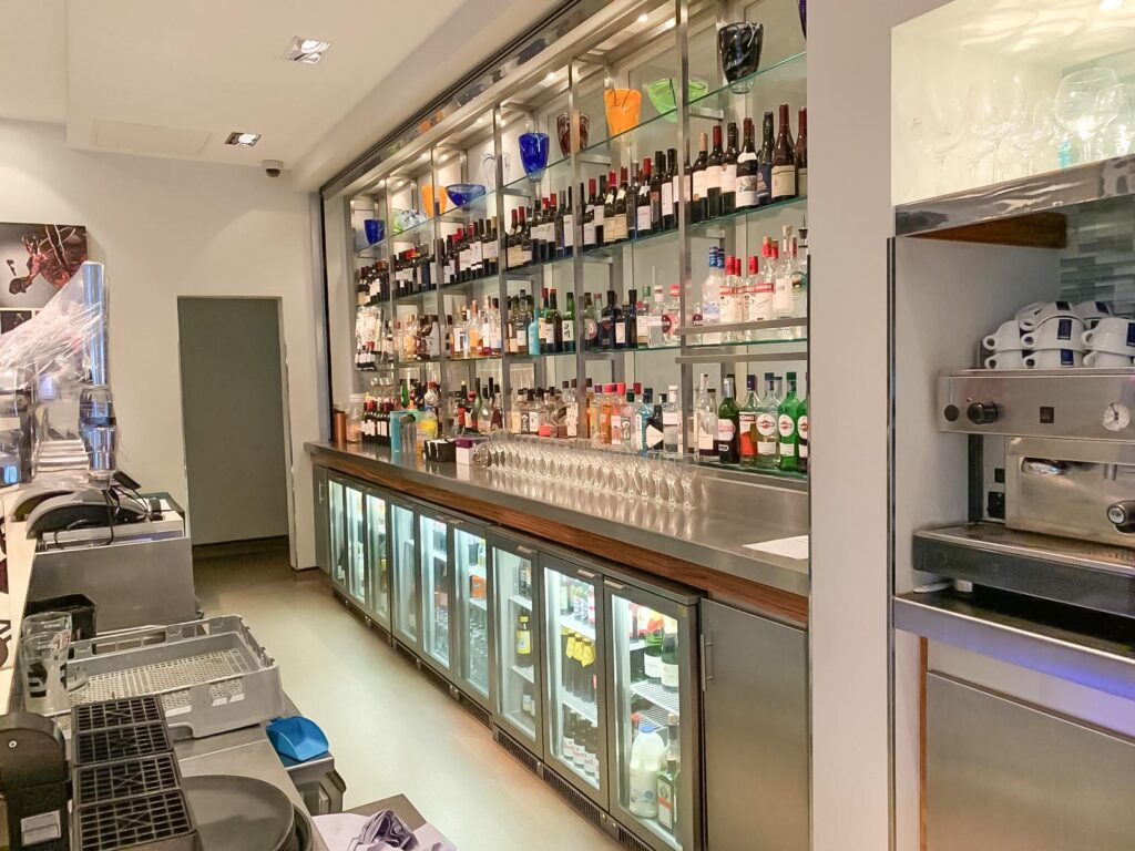 Behind a bar at the Holiday Inn with shelves of drinks and fridges