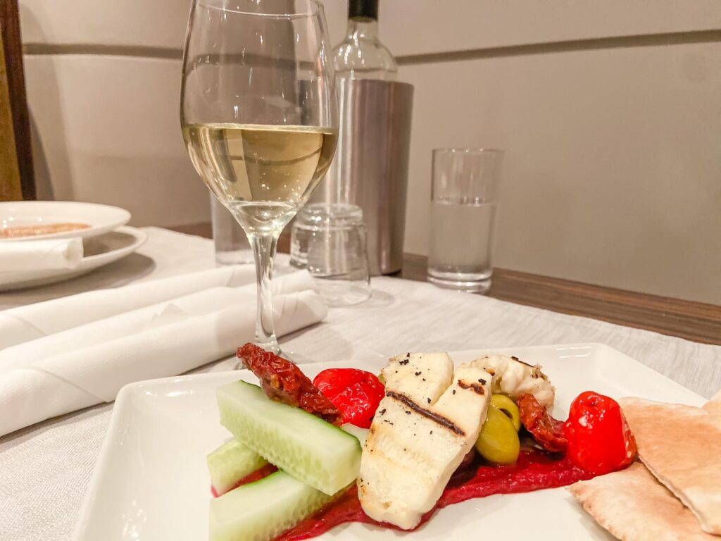 A plate of food including halloumi, peppers, cucumber and pitta bread on a table with a glass of white wine behind it at a Holiday Inn in Reading on a spa break with friends