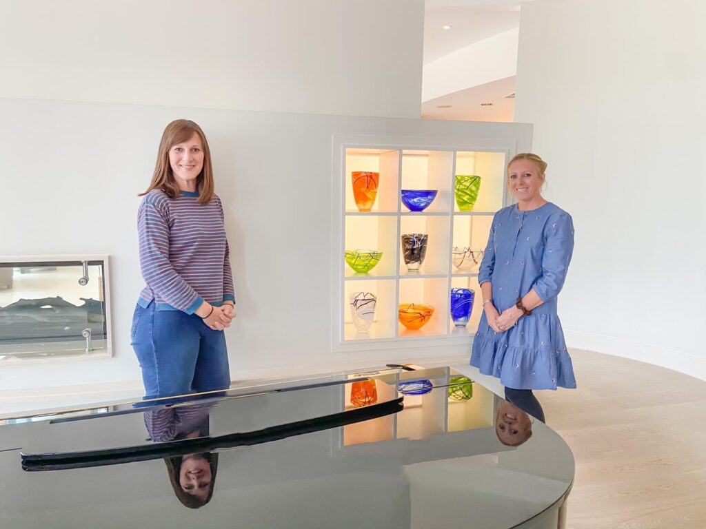 Two women standing next to a wall with a shelf of colourful vases and a grand piano in front