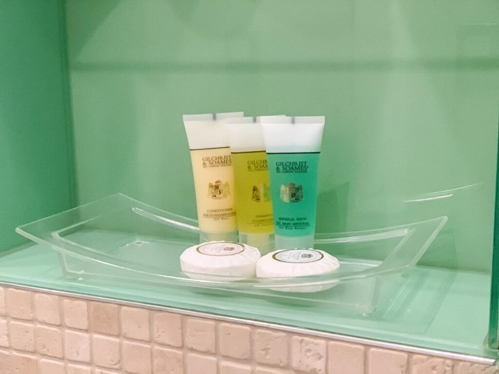 Glass shelf in a bathroom with three different coloured bottles of toiletries