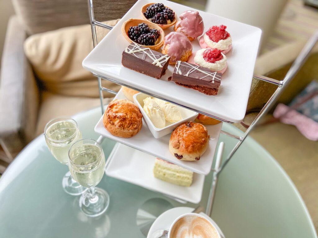 A stack of plates on a tower with an afternoon tea on it including scones, cakes and sandwiches, alongside a cup of coffee and two glasses of champagne at a spa break with friends