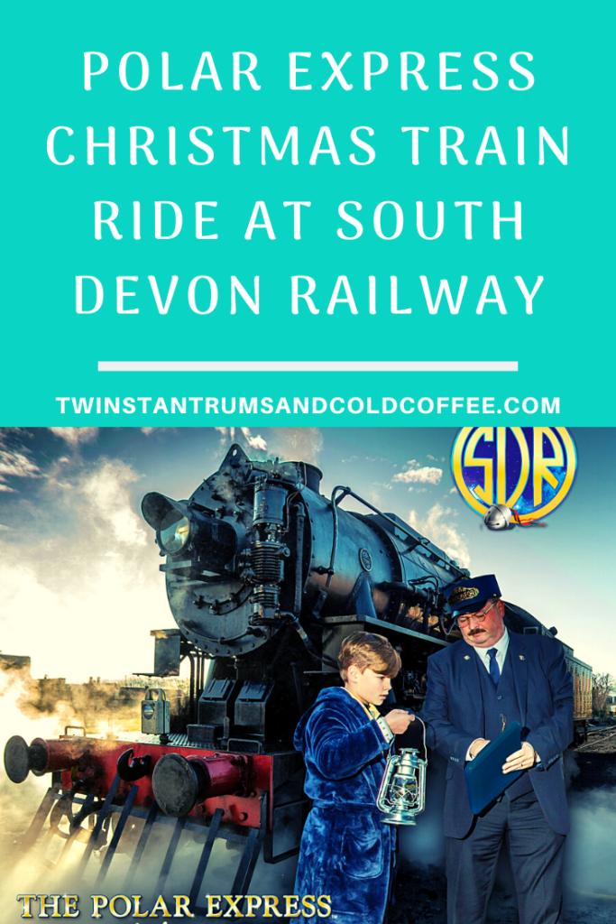PIN for the Polar Express Christmas train ride at South Devon Railway, a boy in a dressing gown talks to a conductor on a platform in front of a steam train