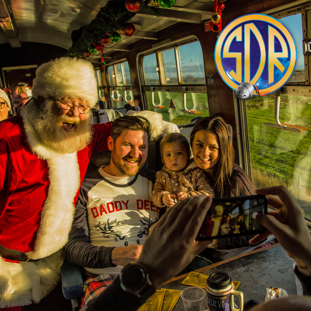 Father Christmas chats to a man and woman with their toddler girl in the carriage of a steam train
