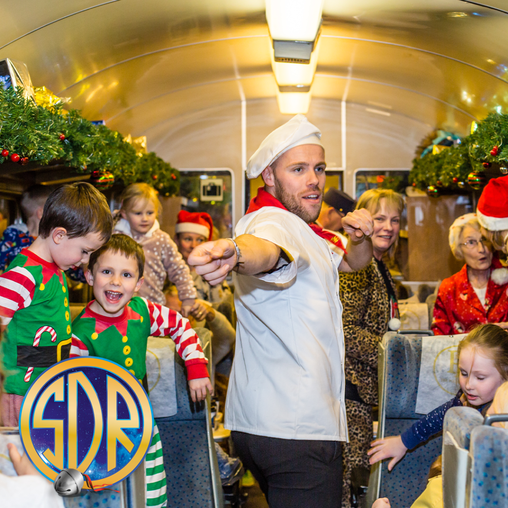A man dressed as a chef dances in the aisle of the Polar Express surrounded by smiling children in their seats wearing Christmas pyjamas