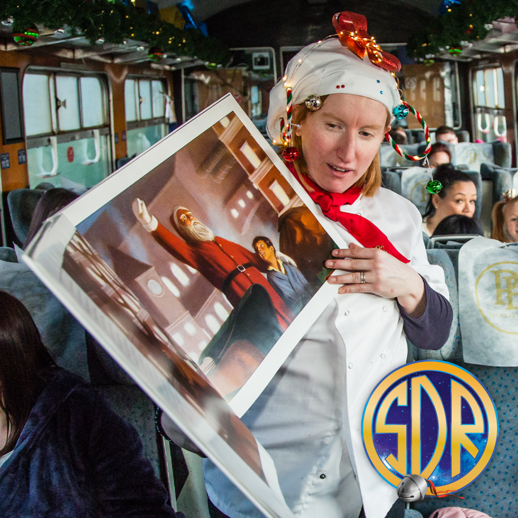 A woman dressed as a chef with festive hat on holds a large story book of the Polar Express and reads to children in a steam train carriage