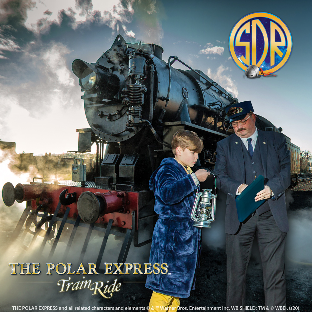 A young boy in pyjamas and dressing gown talks to a train conductor in front of the Polar Express steam train with smoke in the sky