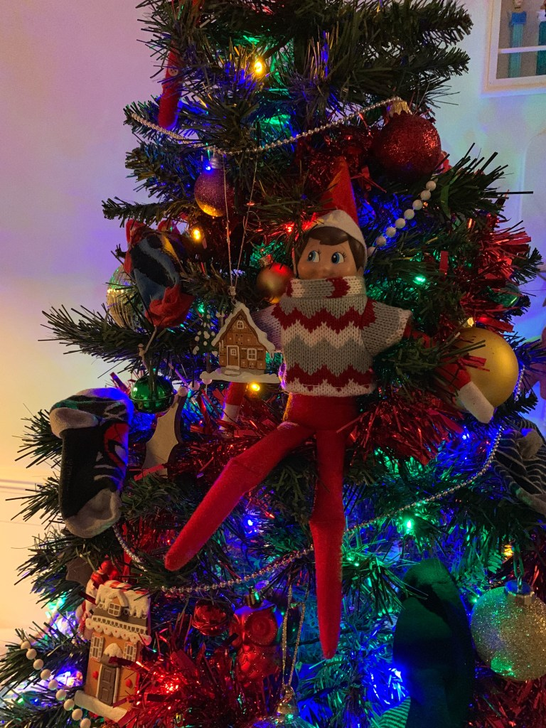 Elf toy hanging in a Christmas tree