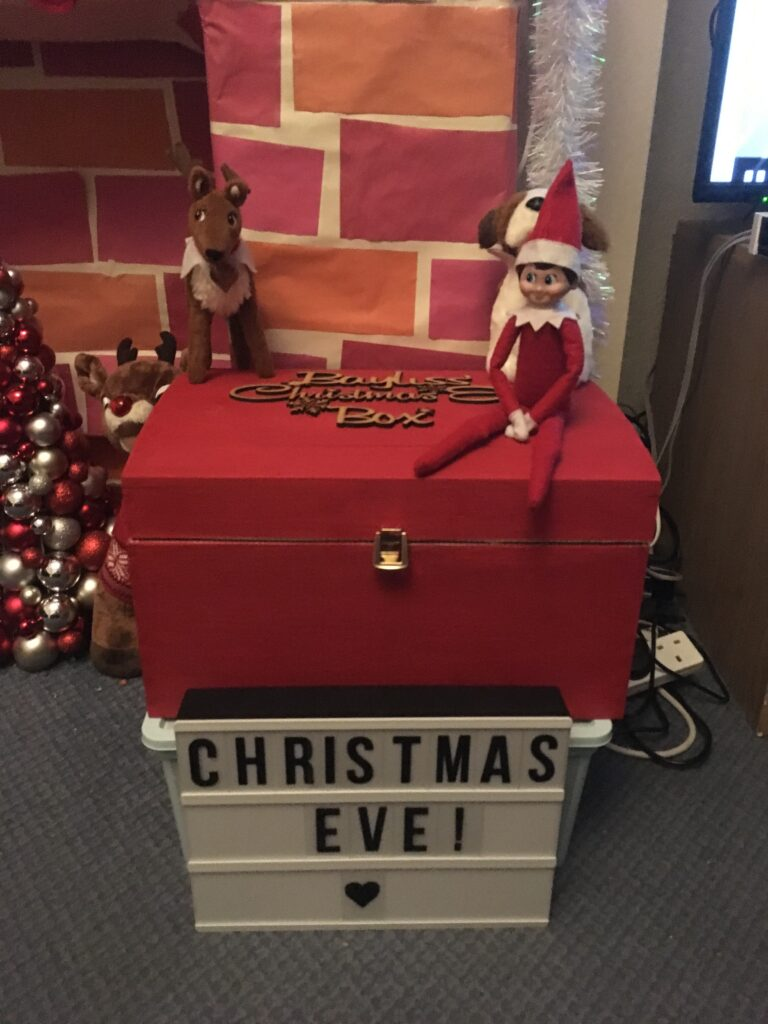 Elf toys on top of a Christmas eve box in front of the fire place
