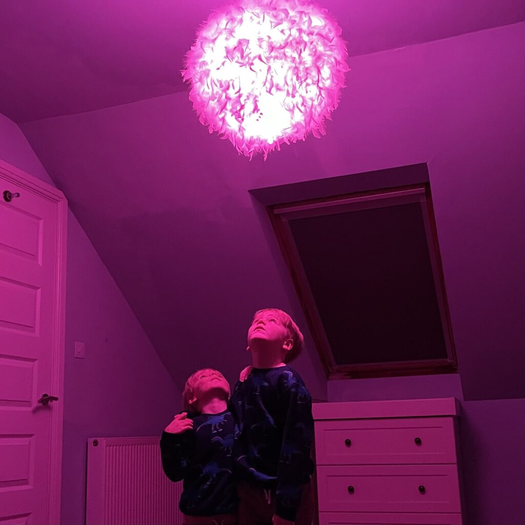 Two boys in a bedroom look up at a pink light turning the room pink with Hive smart home colour changing lightbulbs