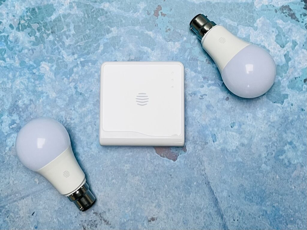 Two lightbulbs and a square white Hive hub box on a blue background