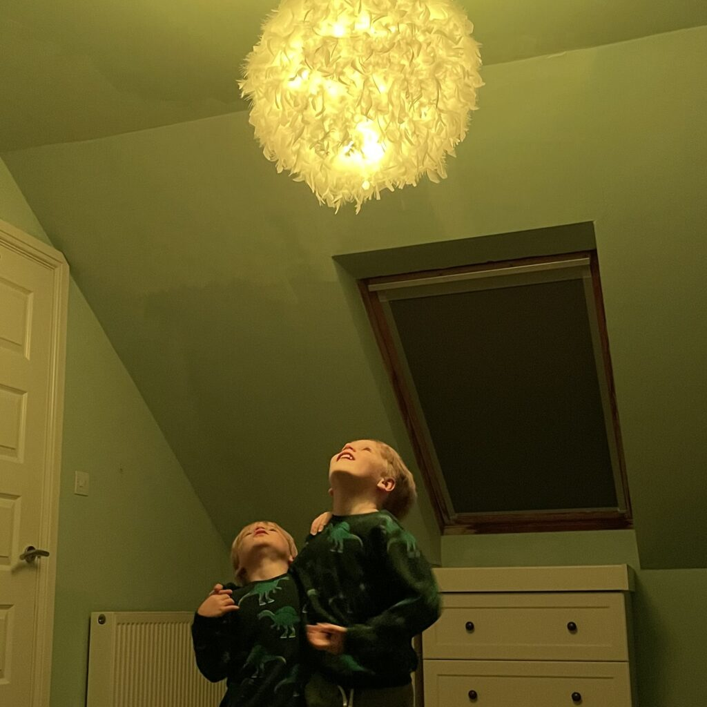 Two boys in a bedroom look up at a yellow feather light turning the room yellow with Hive smart home colour changing lightbulbs