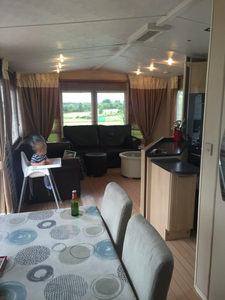 Interior of a caravan in France with a toddler and highchair in