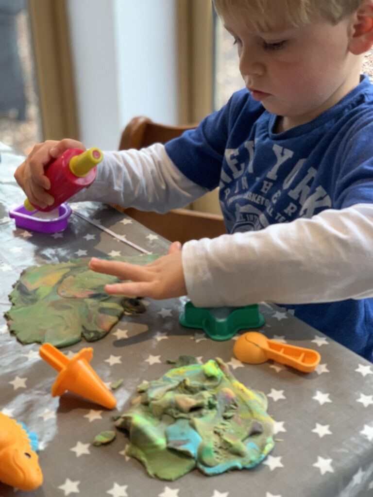 Three year old boy wearing blue t shirt plays with play doh on a kitchen table