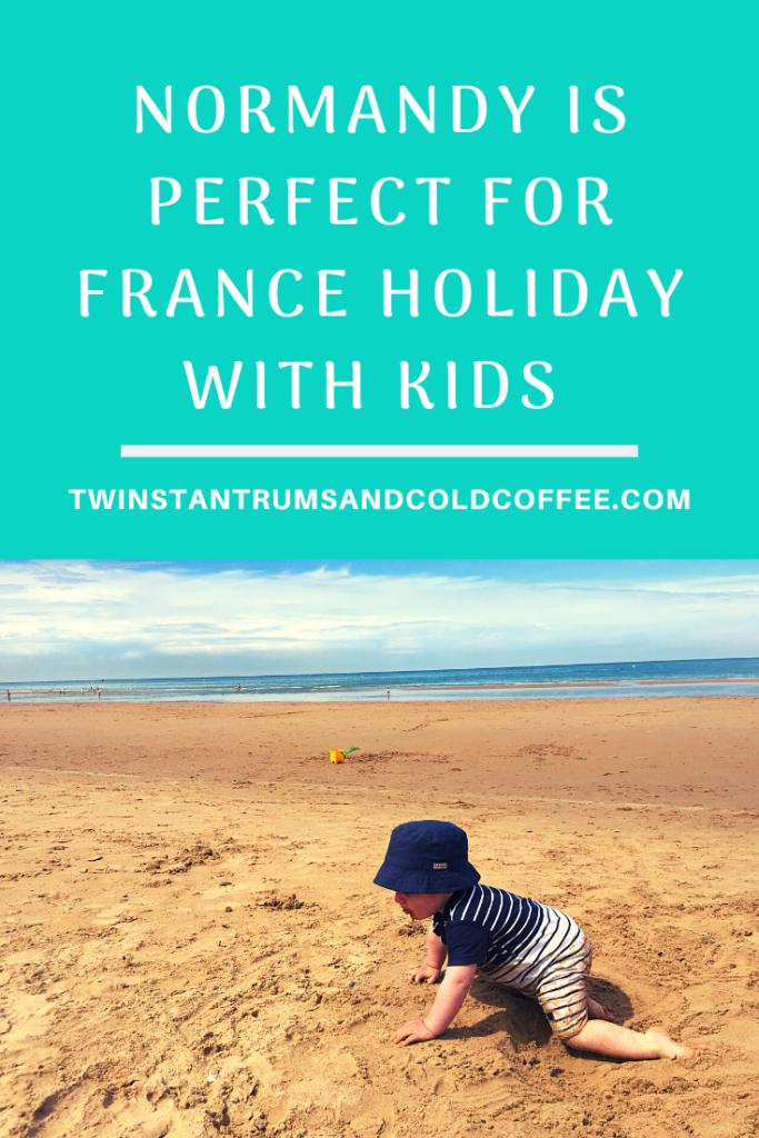 PIN image of a little toddler crawling along the sand with the sea in the background in Normandy