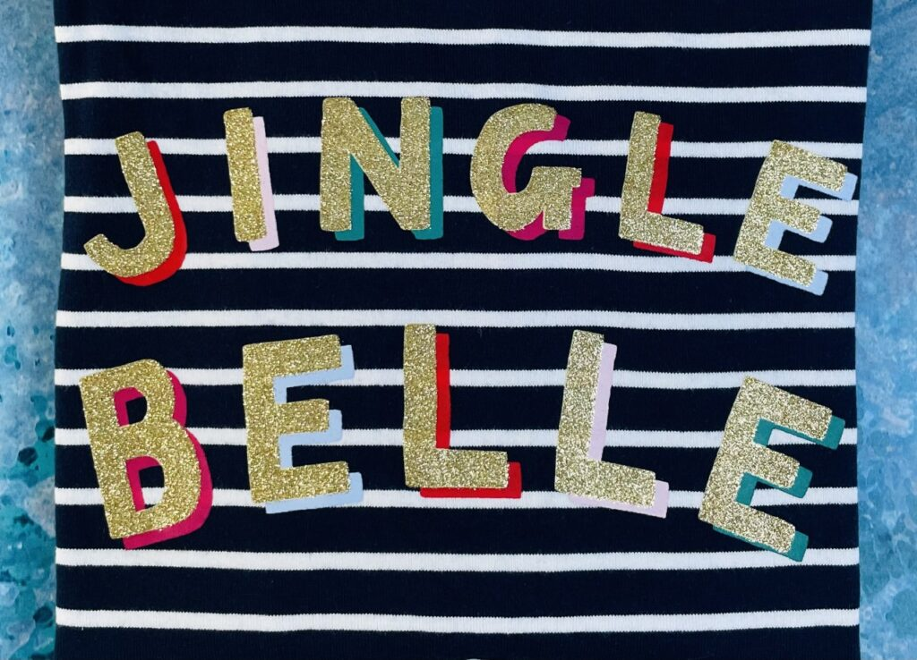 Glittery 'Jingle Belle' slogan on a navy and blue stripey t-shirt