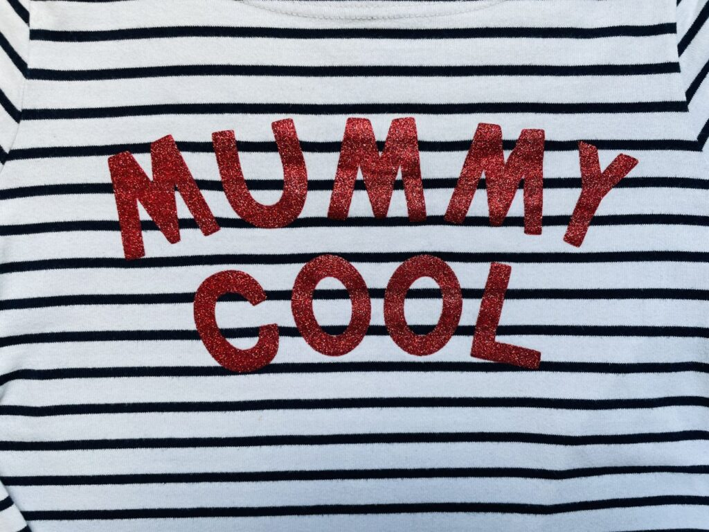 Red glittery 'Mummy Cool' slogan on a black and white stripey t-shirt