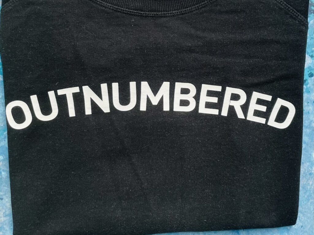 'Outnumbered' slogan in white writing on a black sweatshirt