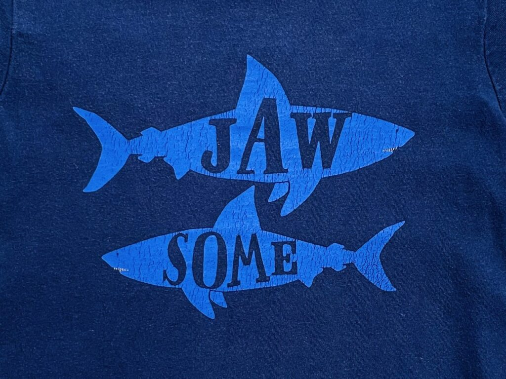 The word 'jawsome' in two sharks as a slogan on a navy shirt