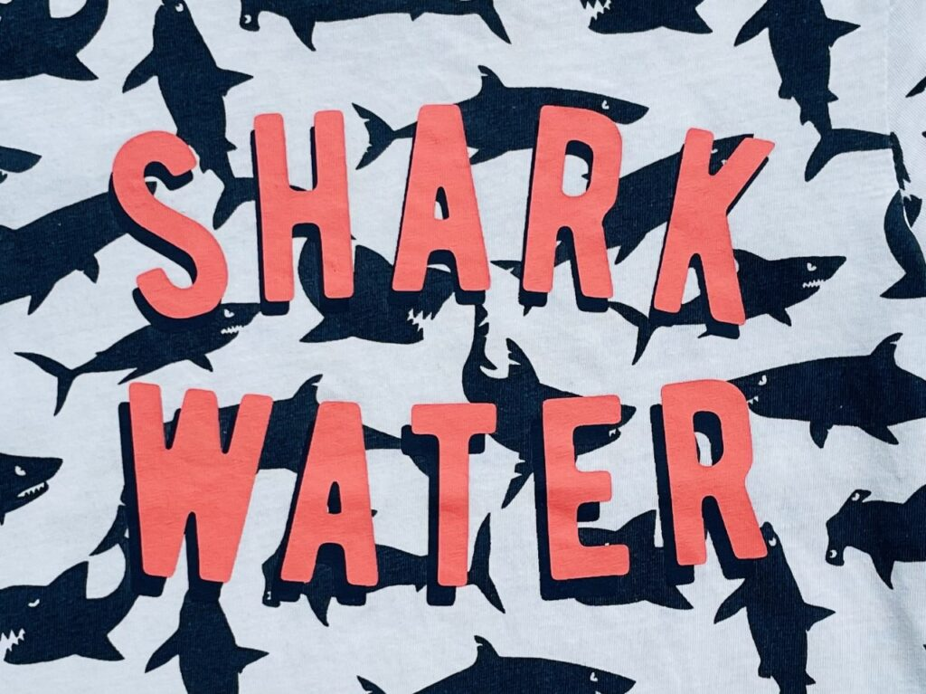 Pink 'shark water' slogan on a white t-shirt with navy sharks on it