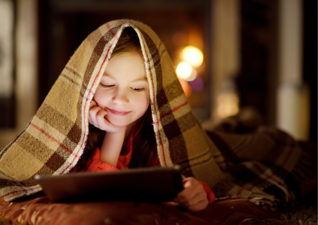 A girl with a tartan blanket over her head watching a tablet in front of the fire for a Christmas movies for kids post