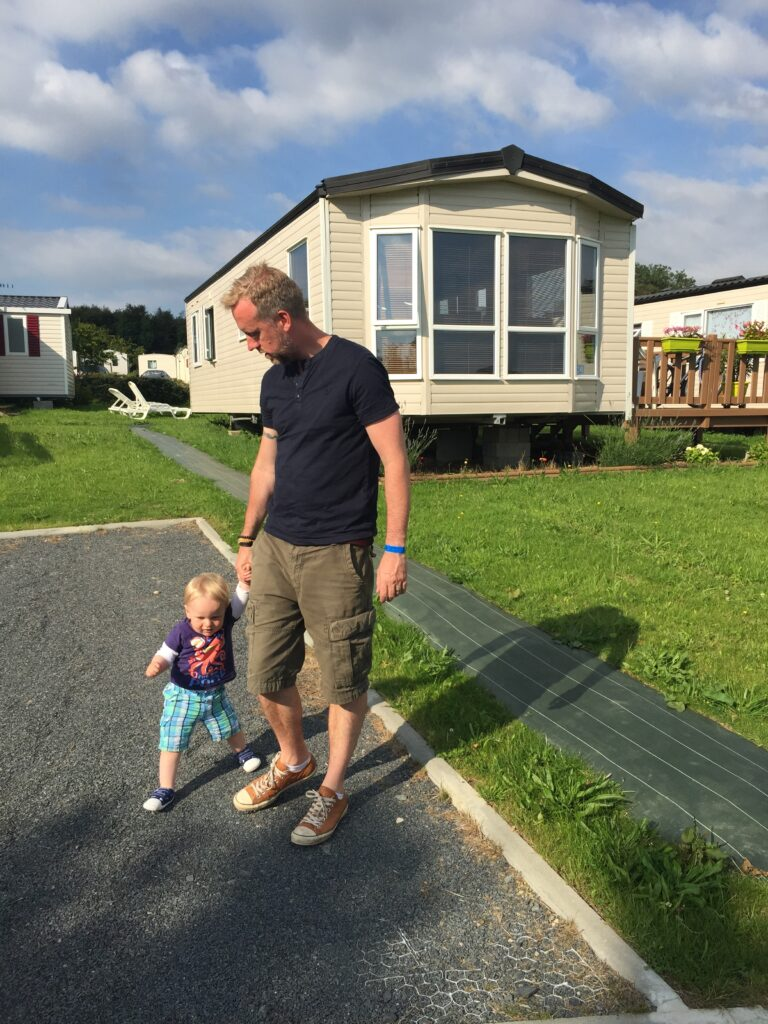 Dad and toddler son holding hands and walking outside a caravan in France