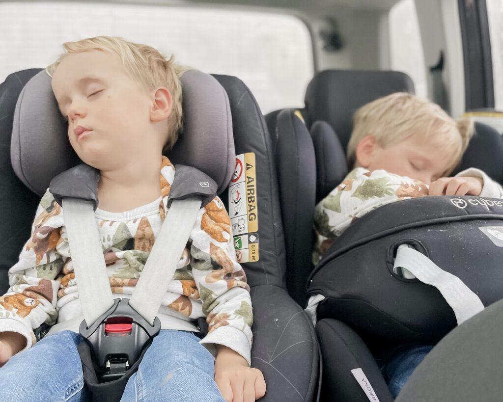 Three year old twin boys both asleep in their car seats