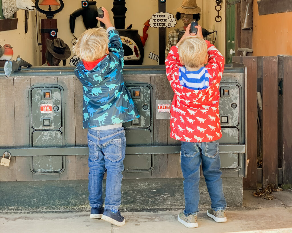Three year old twin boys wearing a blue coat and red coat, and jeans stretch up to hold the guns on a shooting game at Pennywell Farm.
